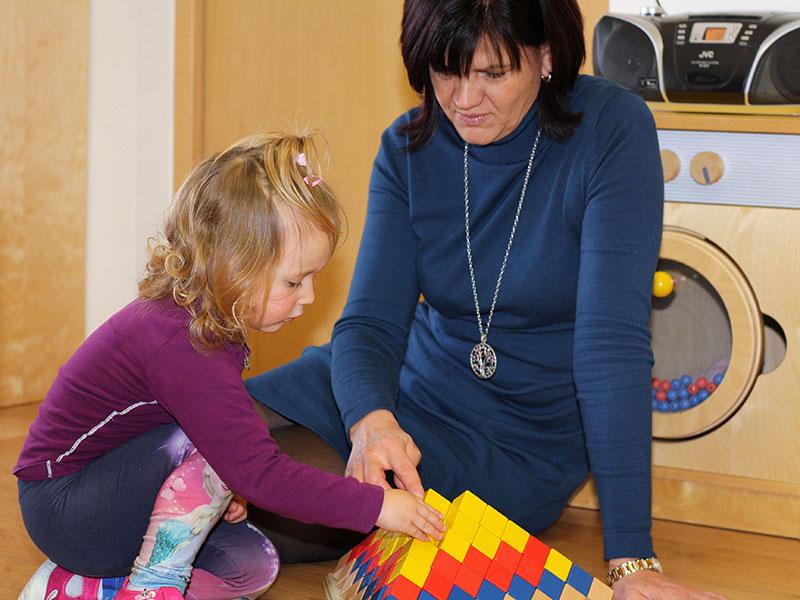Pädagogin spielt mit Mädchen